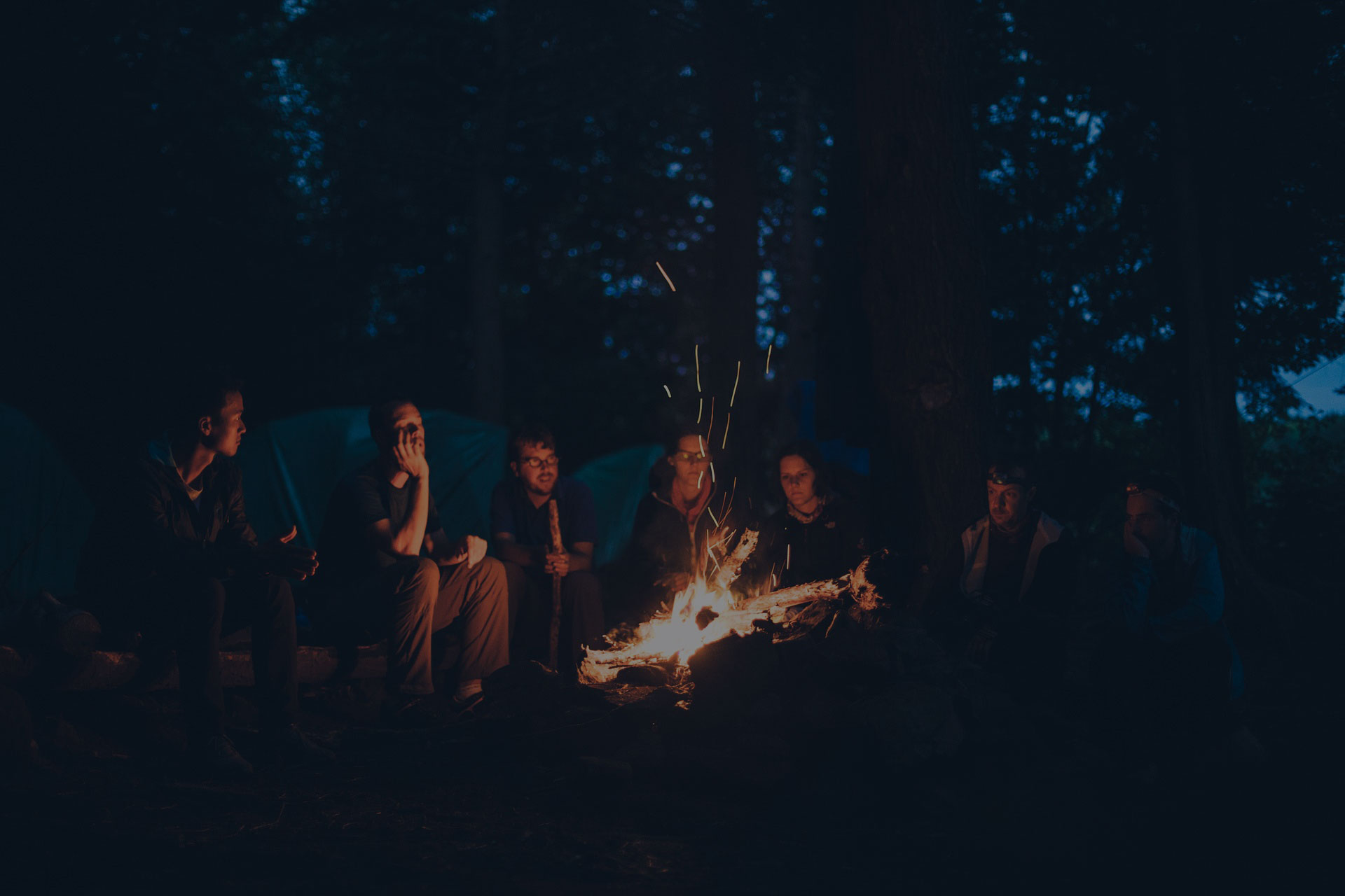 Group of backpackers relaxing near campfire after a hard day